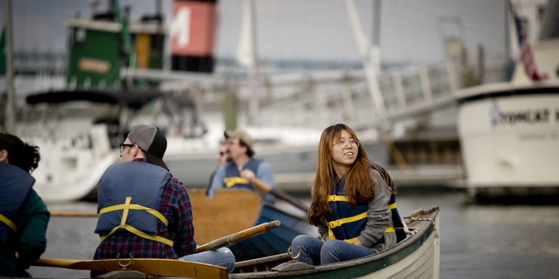 students and professor on a row boat