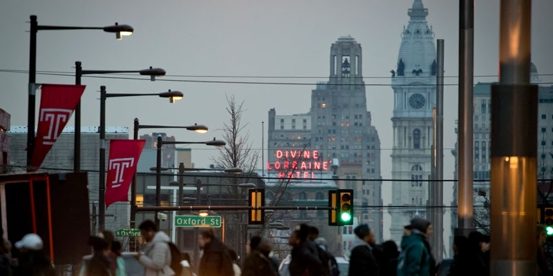 People crossing Broad Street on Temple's campus with City Hall in the background