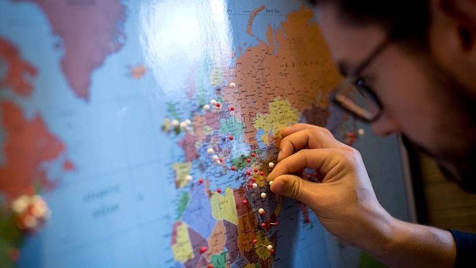 a student placing a pin on a world map