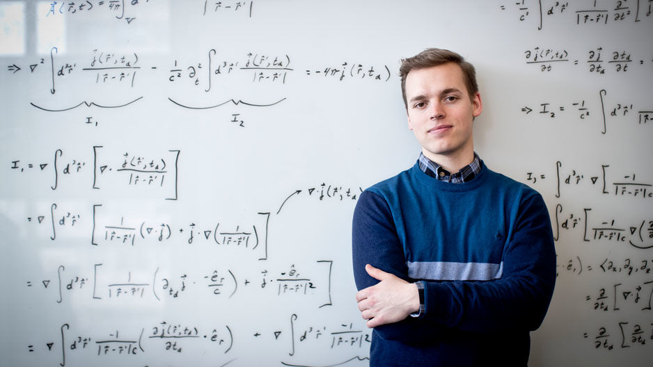 Marcus Forst in front of a whiteboard filled with equations
