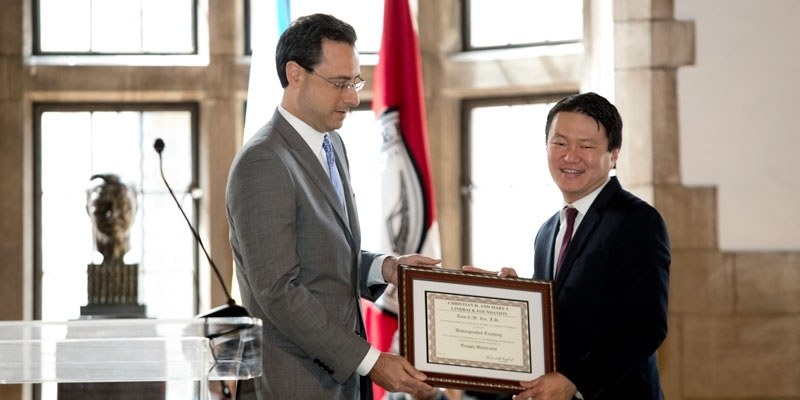 Tom C.W. Lin accepts a Lindback Award from Law School Dean Greg Mandel