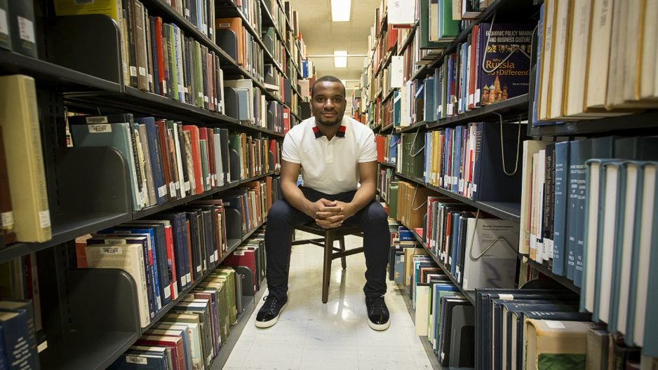 Hazim Hardeman sitting among the stacks at Paley Library.
