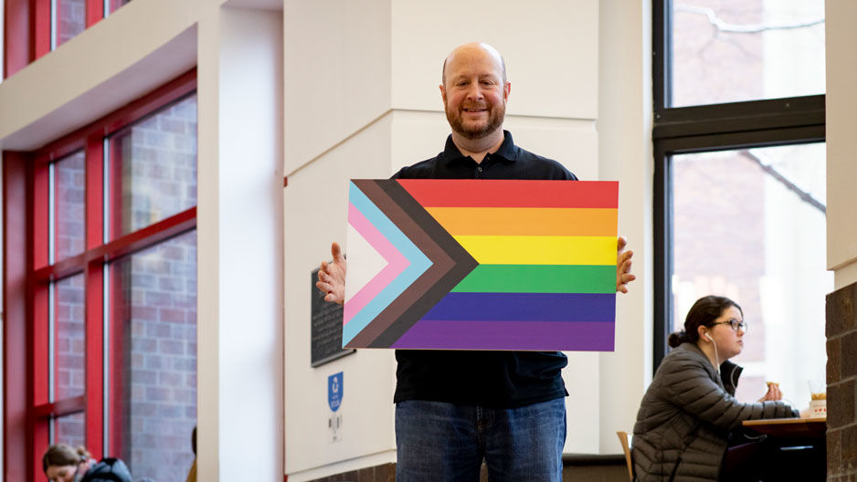Jason Levy holding the Progress Pride flag