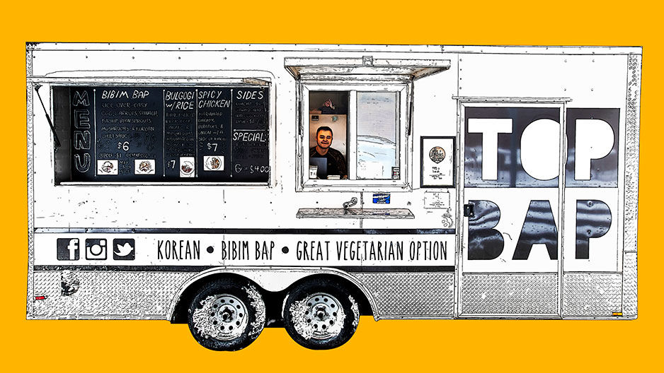 A still image of a man behind the Top Bap food truck.