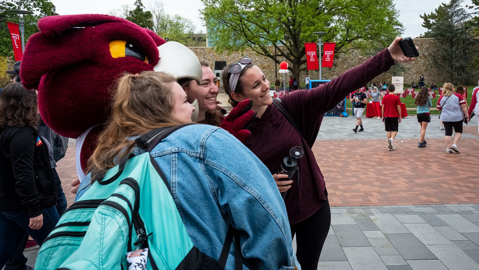 Students taking a selfie with Temple mascot Hooter