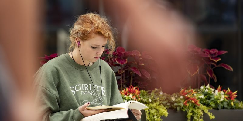 A student reading outside Temple's Charles Library