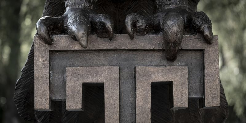 "a close up of Main Campus' Owl statue's talons gripping the Temple ""T"""