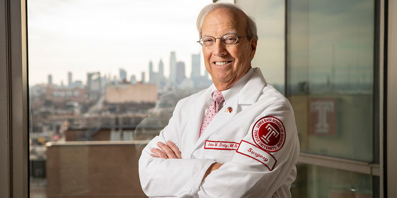 Dean Daly standing before a window with a view of the Philadelphia skyline.