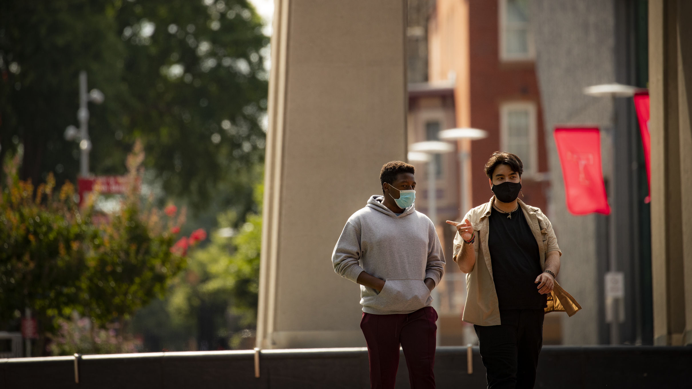Image of two students wearing face coverings walking down Polett Walk on Main Campus.