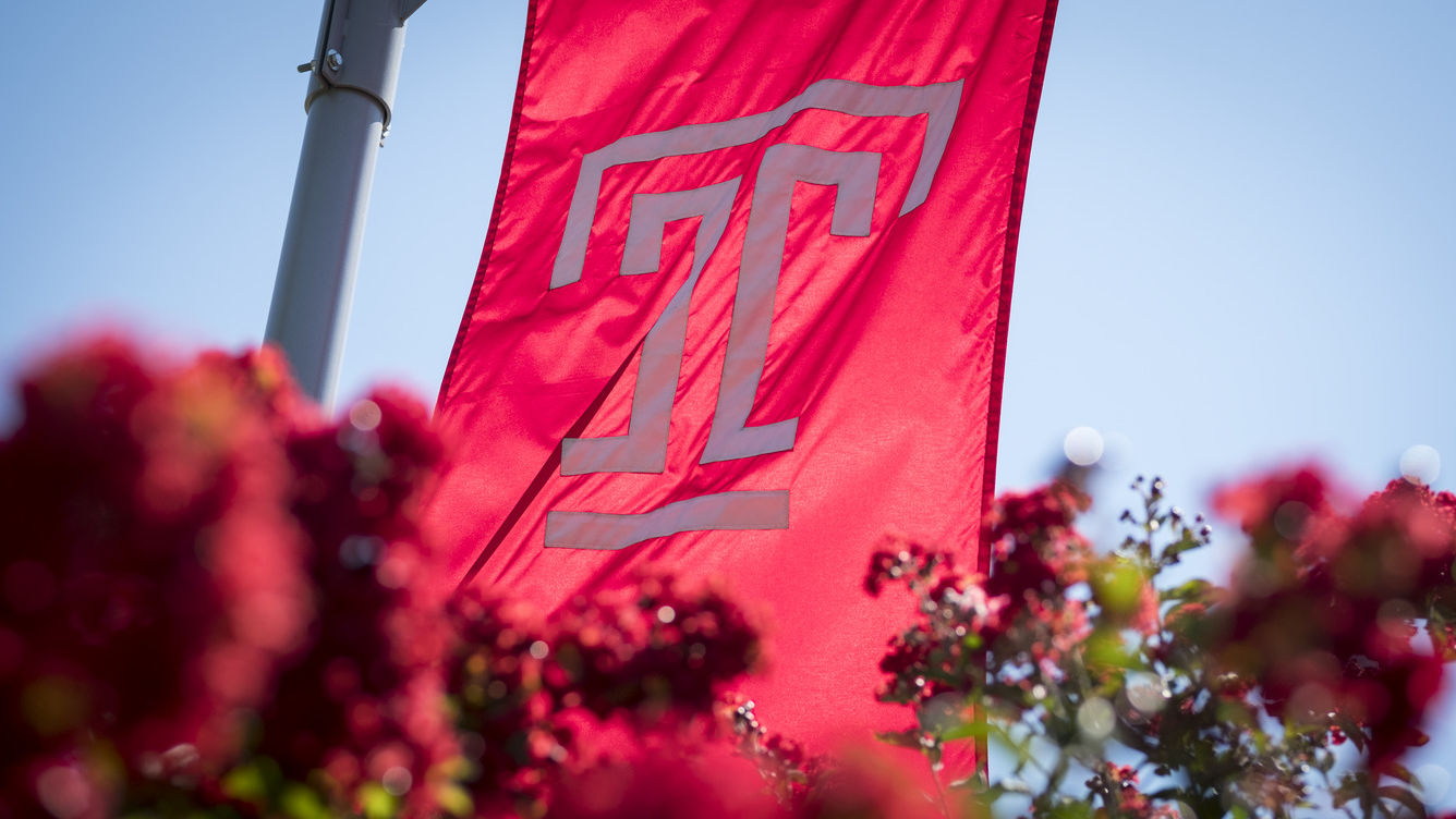 Temple flag flying above red flowers.