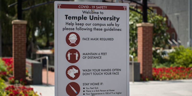 a sign on campus describing COVID-19 health precautions
