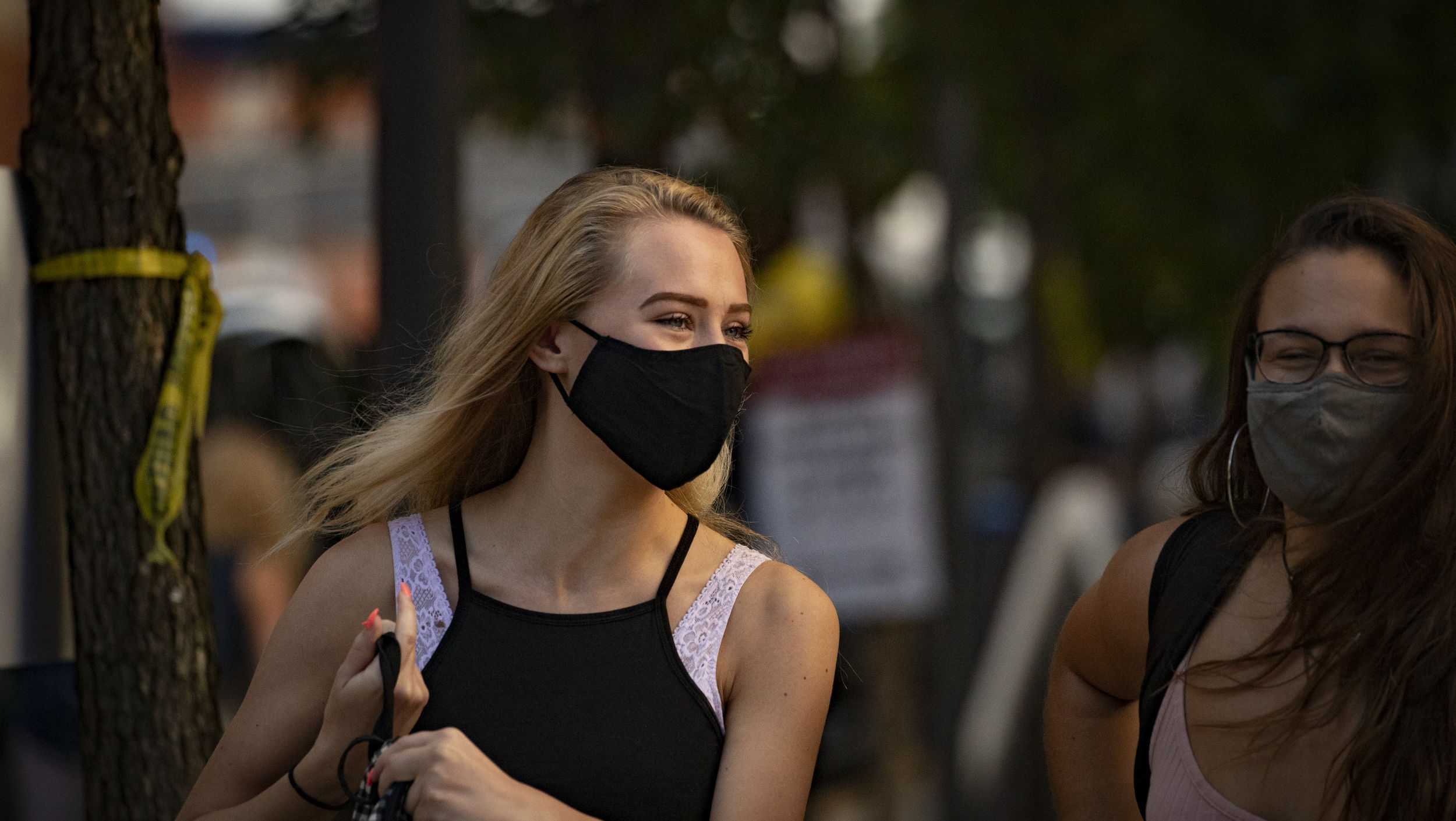 Two students smiling and wearing masks on campus