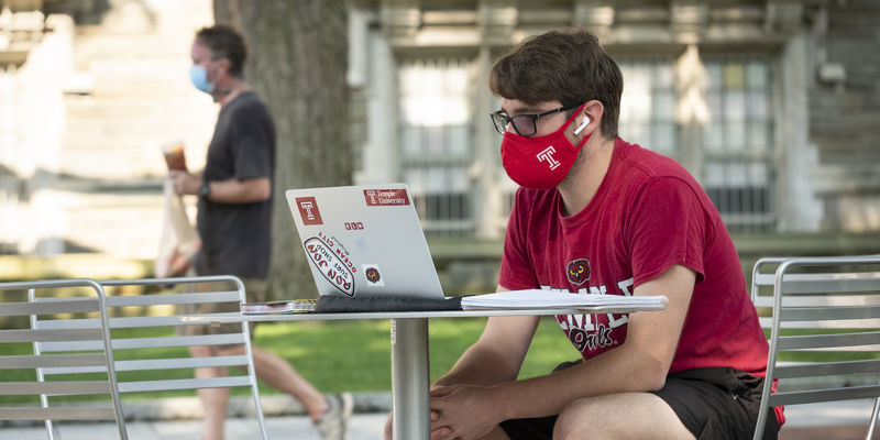 A student sitting outside on campus wearing a mask while using their computer.