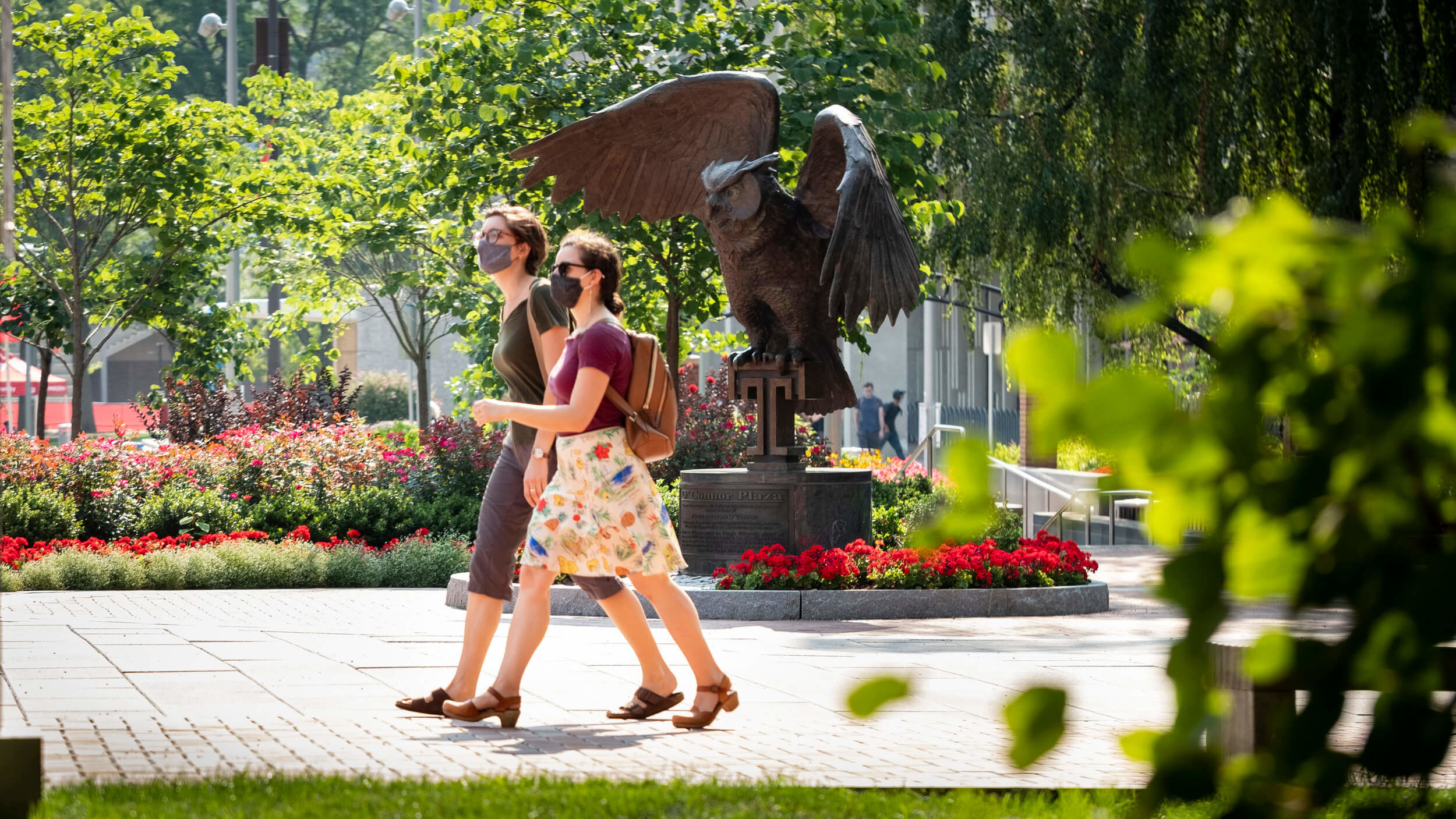 Two students wearing masks walk past an owl statue on Temple's Main Campus.