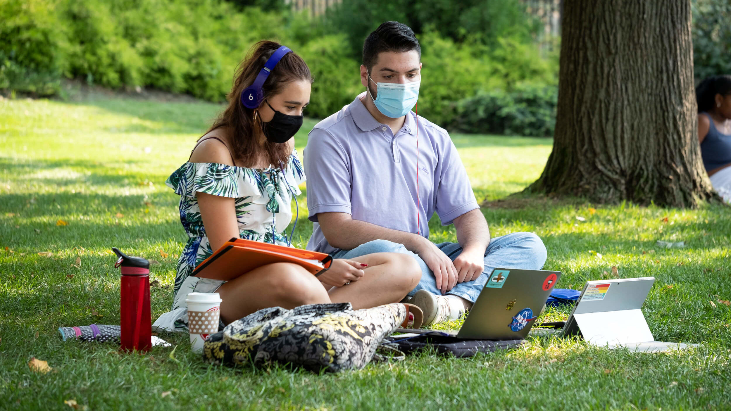 Two Temple students wearing masks study outside on Main Campus.