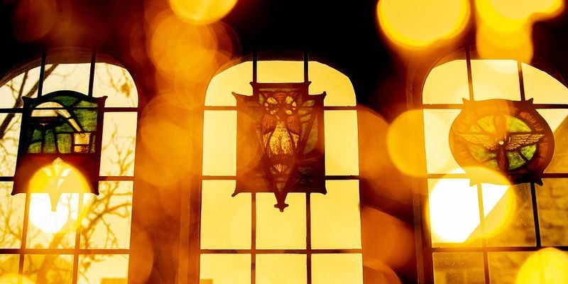 The sun shining through the stained glass windows of Mitten Hall's Great Court.
