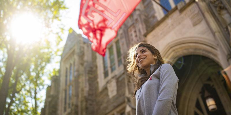 Jennifer Sierra standing under a Temple flag.