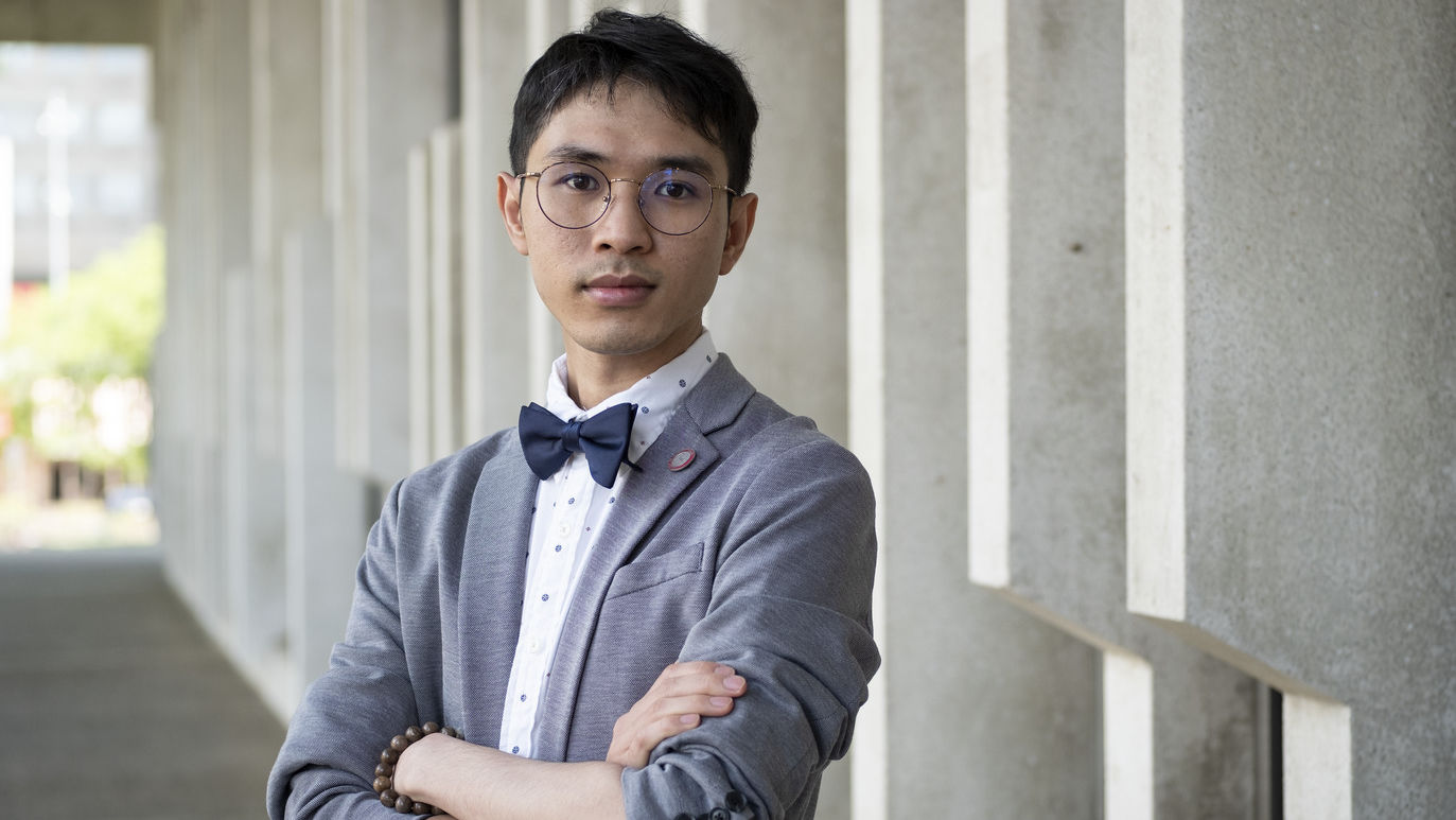 Hoa Vo standing in front of a building, wearing a bow tie.