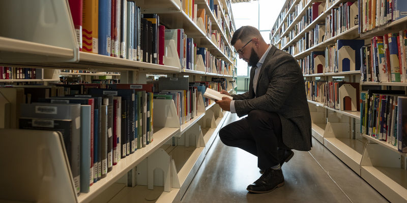 Image of student looking through bookshelves at Charles Library.