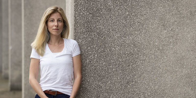 Jennifer Pollitt standing in front of a concrete building, wearing a white t-shirt.