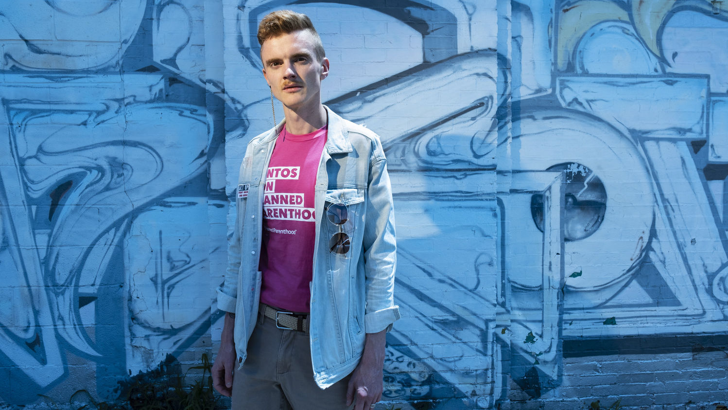 Andreas Copes in front of a blue background, wearing a Planned Parenthood shirt.