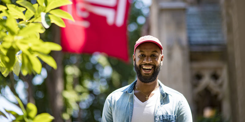 Brice Izyah smiling, wearing a red hat and standing under a Temple flag.