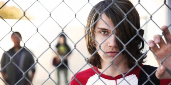 A male teen from the documentary 'The Bad Kids' holding a chain link fence.