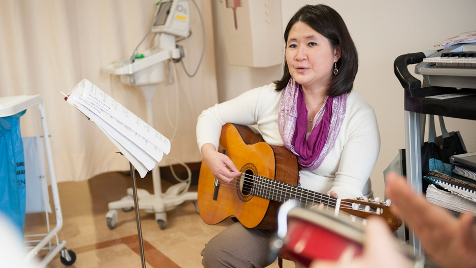 A woman with a guitar in a hospital room