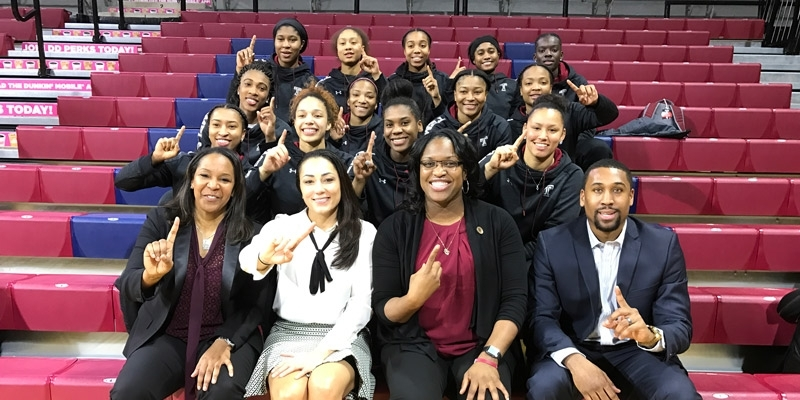 the Temple women's basketball team holding up their fingers to signify No. 1.