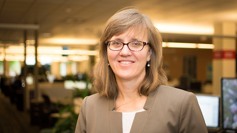A woman wearing glasses and a brown blazer.