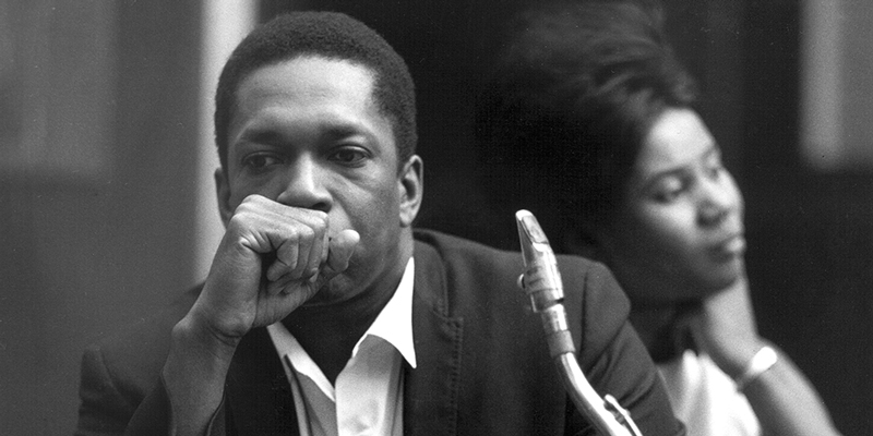 Coltrane sitting with his saxophone.