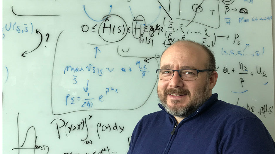 Associate Professor of Biology Vincenzo Carnevale in front of white board with equations