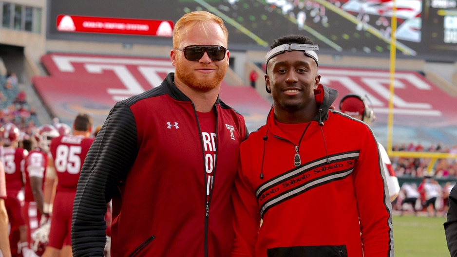 Two men standing on the sideline of a Temple football game.