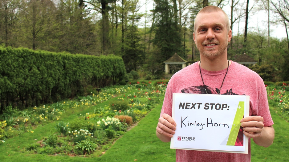 A man in a garden holding a sign that reads Next Stop: Kimley Horn.