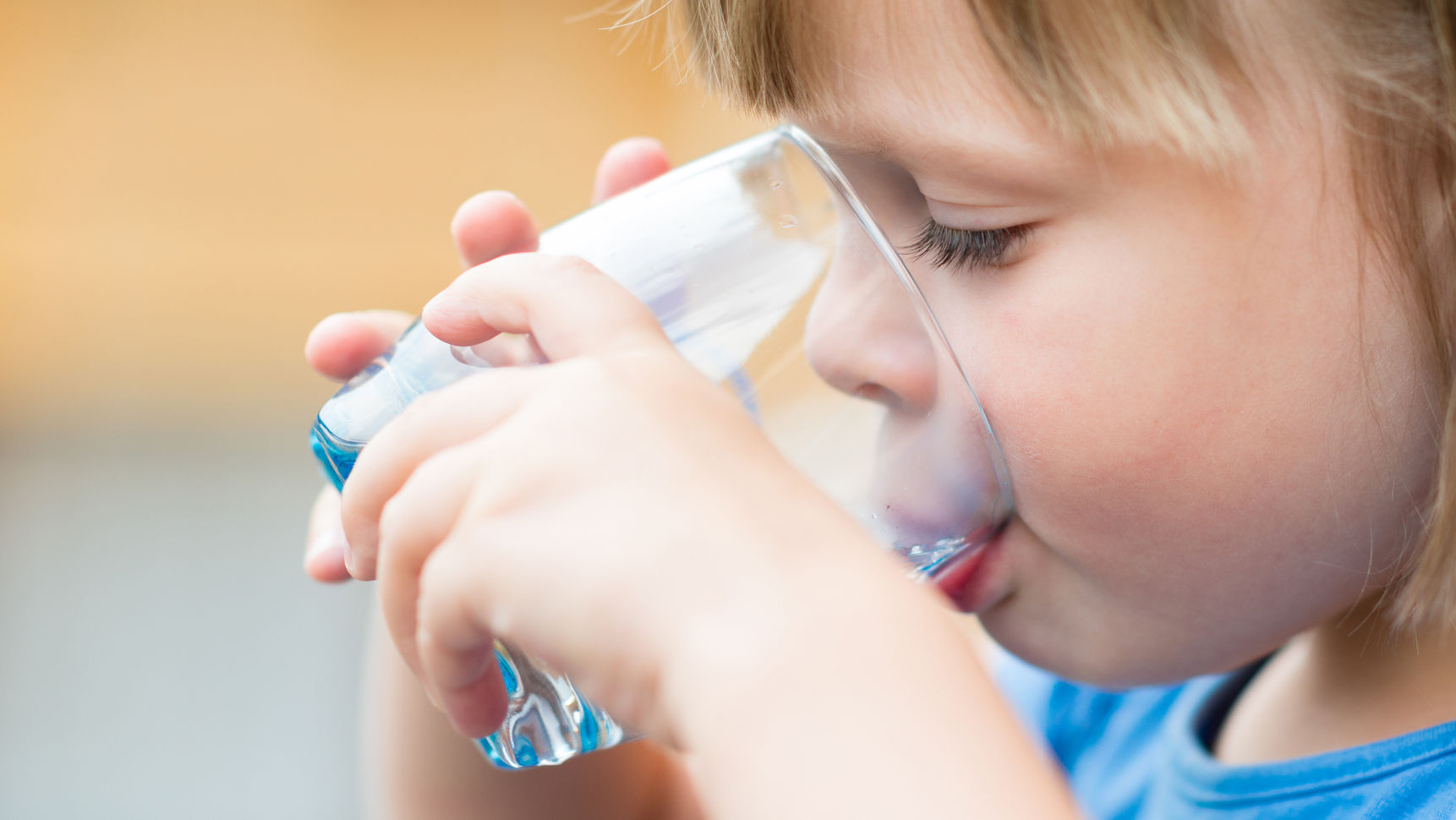 a toddler drinking a glass of water