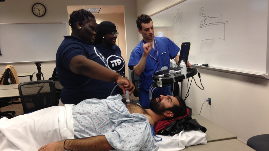 Two medical students showing middle school students a procedure in the hospital.