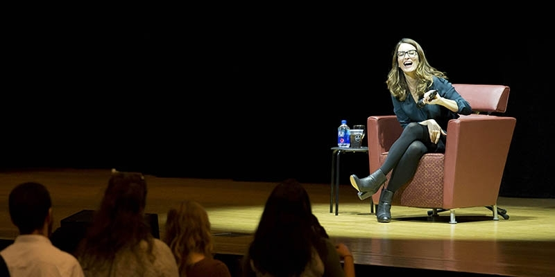 Tina Fey sitting on stage while holding a microphone and laughing.