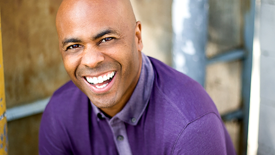 Fred Thomas Jr. wearing a purple shirt and smiling