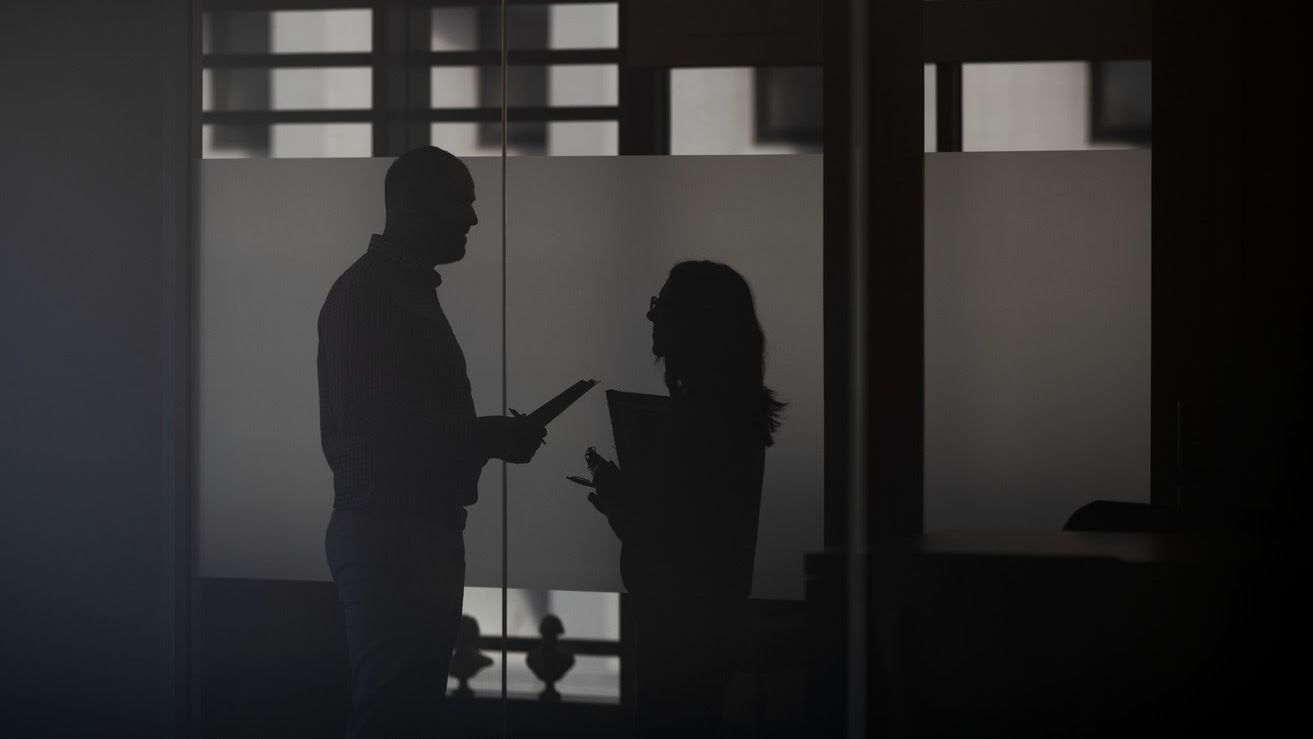 Two profiled silhouettes of two staff members talking with each other.