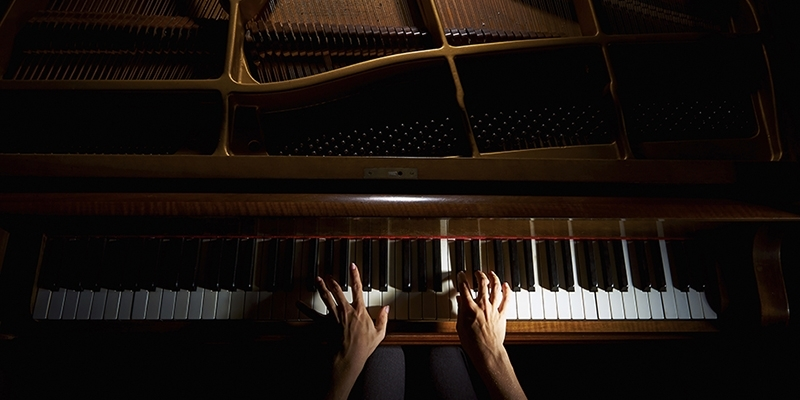 Hands playing a piano.