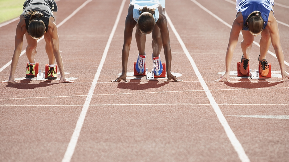 Women runners kneeling on the track before a race starts.