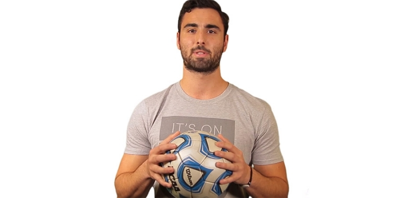 A male Temple soccer player wearing a gray T-shirt and holding a soccer ball.