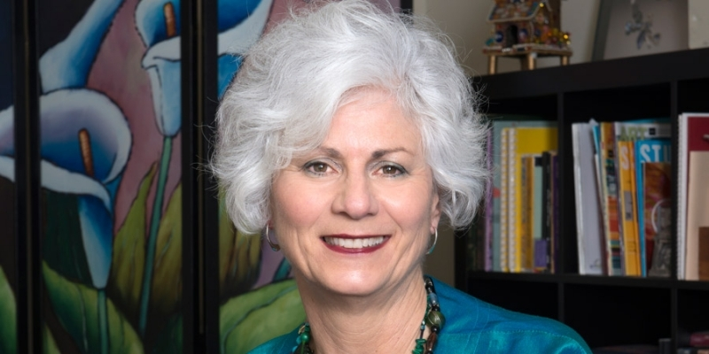 Lisa Kay wearing a teal jacket and standing in front of a bookcase.