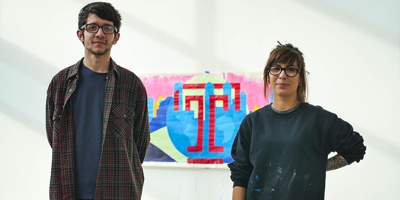 A man and woman standing in front of a painting.