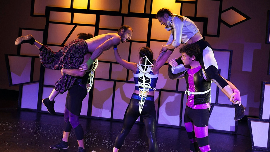 Dancers lifting each other up on stage with purple lighting.