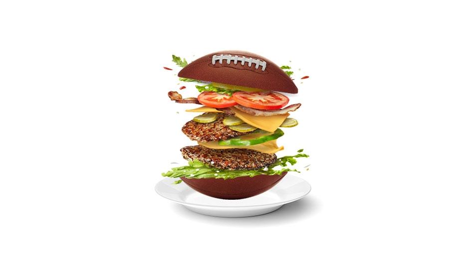 An illustration of a double bacon cheeseburger that has a football as a bun.