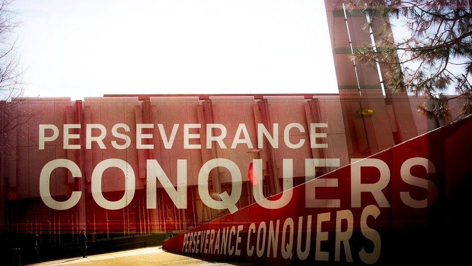 a sign that says Perseverance Conquers