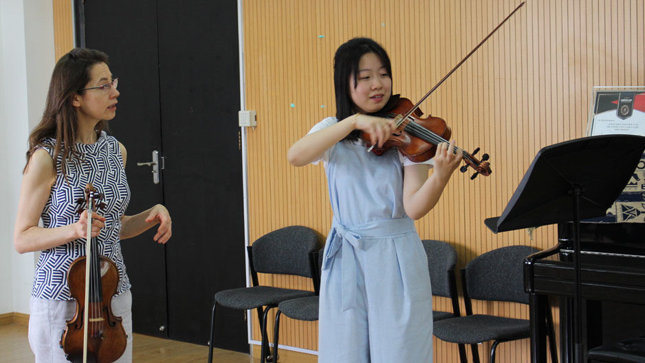 A Boyer professor instructing a student in violin