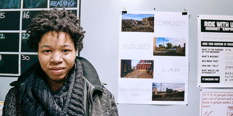 Rasheedah Phillips standing in front of a wall with a calendar and posters.