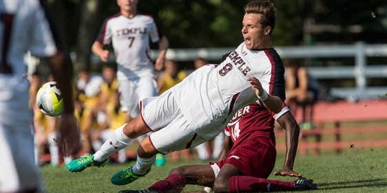 A Temple men's soccer player kicking the ball during a match.